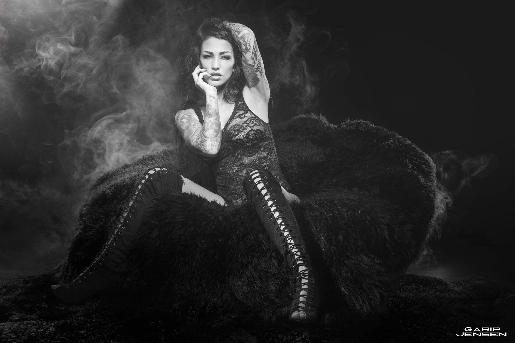 sexy tattooed model, in black and white, sitting on a fur sofa in a smoky studio