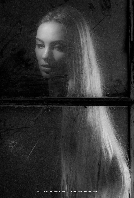 Beautiful blond model, behind a dirty window.