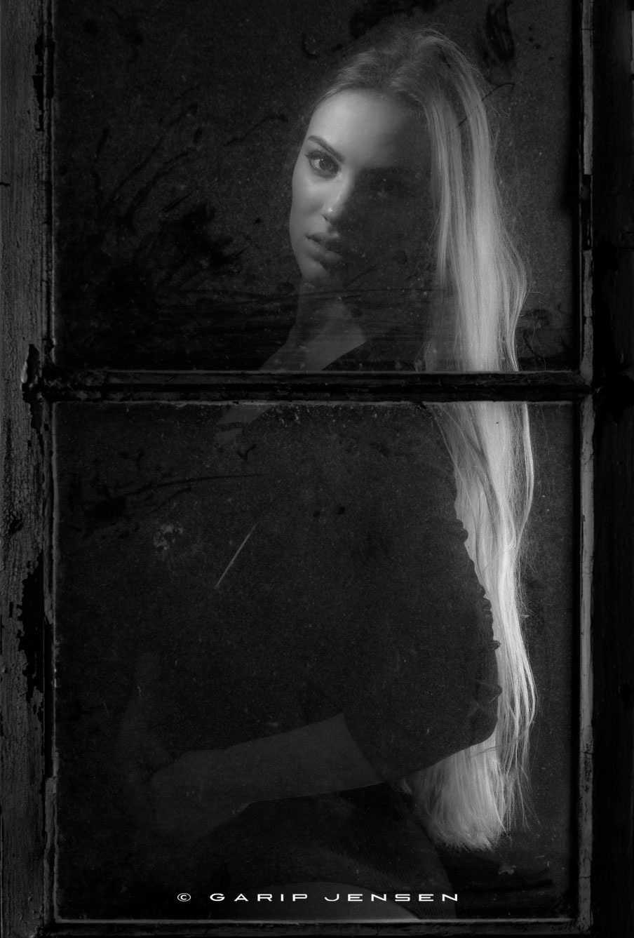 young beautiful Swedish model, photographed behind a dirty window